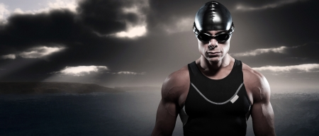 Swimmer triathlon man with cap and glasses outdoor at rough sea with stormy dark sky. Extreme fitness sport. Stock Photo