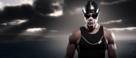 Zwemmer triathlon man met pet en bril buiten op ruwe zee met stormachtige donkere hemel. Extreme fitness sport.