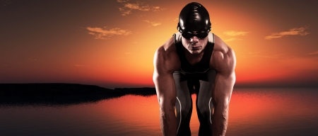 Swimmer muscled triathlon man with cap and glasses outdoor at a lake at sunset. Extreme fitness sport. Panorama shot. photo