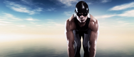 Swimmer triathlon muscled man with cap and glasses outdoor at a lake with blue cloudy sky. Extreme fitness sport. Standard-Bild