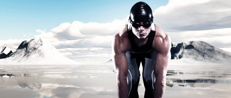 frozen lake: Swimmer triathlon muscled man with cap and glasses outdoor at a frozen lake with snow mountains and blue cloudy sky. Extreme fitness sport.