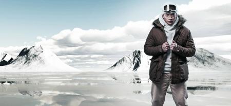 winter fashion: Asian winter fashion man in snow mountain landscape. Wearing woolen hat, jacket and ski glasses.