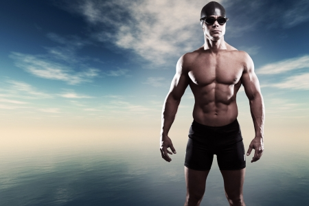Muscled swimmer man with cap and glasses outdoor at a lake with blue cloudy sky. Extreme fitness sport. photo