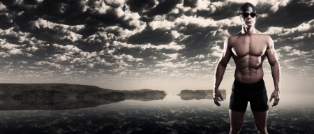 swimmer: Muscled swimmer man with cap and glasses outdoor at rough sea with stormy dark sky. Extreme fitness sport.