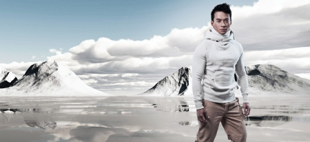 Asian winter fashion man in snow mountain landscape. Wearing white sweater and scarf and brown trousers. Stock Photo