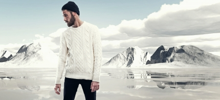 Cool man with beard in winter fashion. Wearing white woolen sweater and black cap. Outdoor in snow mountain landscape.