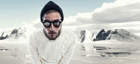 Cool man with beard in winter fashion. Wearing white woolen sweater black cap and sunglasses. Outdoor in snow mountain landscape.