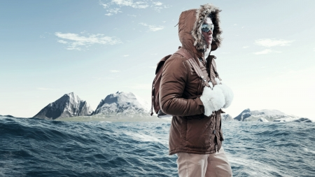 Asian winter sport fashion man with sunglasses and backpack in arctic mountain landscape. Wearing brown jacket with fur hoody and white gloves.