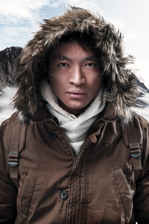 Asian winter sport fashion man with backpack in snow mountain landscape. Wearing brown jacket with fur hoody.