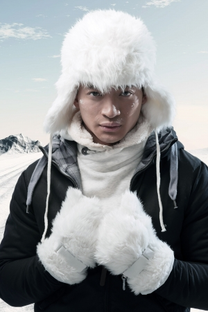 Asian winter fashion man in snow mountain landscape. Wearing black jacket with white furry hat and gloves. photo