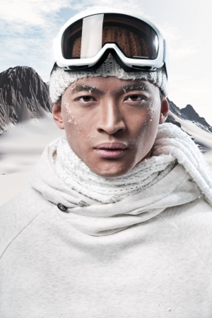 eskimo: Asian winter holiday fashion man in arctic snow landscape. Wearing woolen hat, sweater, scarf and ski glasses. Stock Photo