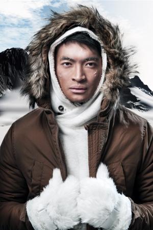 재킷: 눈이 산 풍경에 아시아 겨울 스포츠 패션 남자. 갈색 재킷 모피 후드와 흰색 장갑을 착용. 스톡 사진