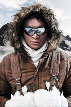 esquimal: Asia hombre de la moda del deporte de invierno con gafas de sol y mochila en el �rtico paisaje de monta�a. El uso de la chaqueta marr�n con capucha de piel y guantes blancos.