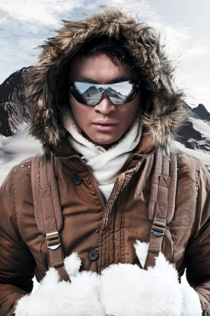 to coat: Asian winter sport fashion man with sunglasses and backpack in arctic mountain landscape. Wearing brown jacket with fur hoody and white gloves.