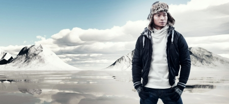 eskimo: Asian winter fashion man in snow mountain landscape. Wearing black jacket with furry hat and gloves.