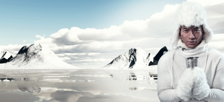 Asian winter fashion man in snow mountain landscape. Wearing white hoody sweater with furry hat and gloves. Holding metal mug. Stock Photo