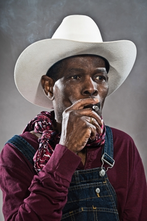 Retro senior afro american blues man in times of slavery. Wearing denim bib and brace overall with white hat. Smoking a cigarette. photo