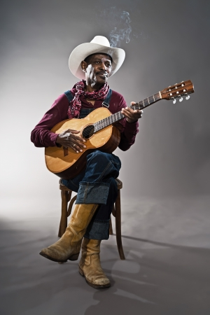 bib overall: Retro senior afro american blues man in times of slavery. Wearing denim bib and brace overall with white hat. Playing acoustic guitar.