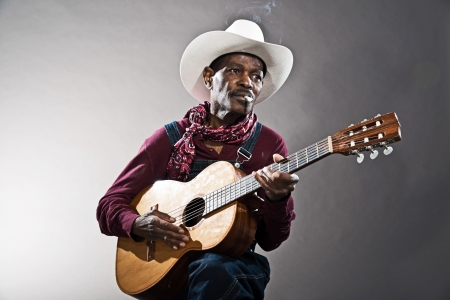Retro senior afro american blues man in times of slavery. Wearing denim bib and brace overall with white hat. Playing acoustic guitar. photo