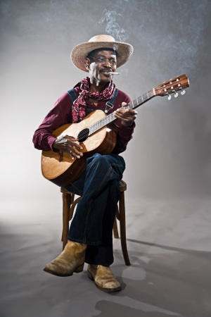 Retro senior afro american blues man in times of slavery. Wearing denim bib and brace overall with straw hat. Playing acoustic guitar. photo