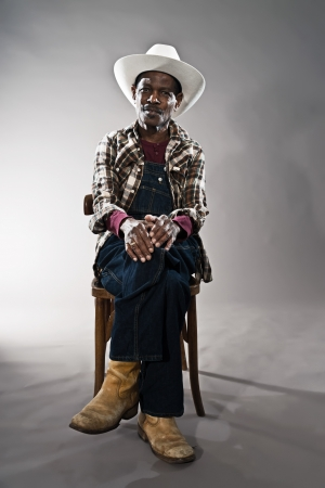bib overall: Retro senior afro american blues man in times of slavery. Wearing denim bib and brace overall with straw hat.