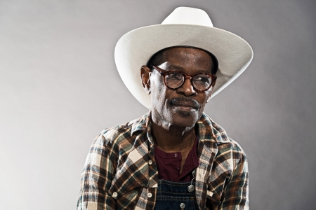 lumberjack shirt: Retro senior afro american blues man in times of slavery. Wearing lumberjack shirt with white hat and glasses.