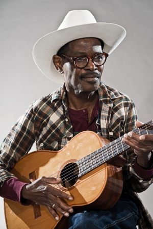 lumberjack shirt: Retro senior afro american blues man in times of slavery. Wearing lumberjack shirt with white hat and glasses. Playing acoustic guitar.