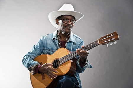 Retro senior afro american blues man in times of slavery. Wearing jeans jacket with white hat and glasses. Playing acoustic guitar. photo