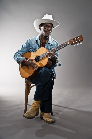 the deep south: Retro senior afro american blues man in times of slavery. Wearing jeans jacket with white hat and glasses. Playing acoustic guitar. Stock Photo