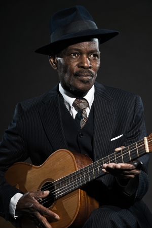 blues: Retro senior afro american blues man. Wearing striped suit with blue hat. Playing acoustic guitar. Stock Photo