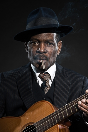 Retro senior afro american blues man. Wearing striped suit with blue hat. Playing acoustic guitar. Smoking cigar.