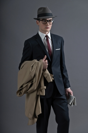 Retro fashion fifties young man with glasses and hat wearing dark suit. Holding a raincoat and newspaper. Studio shot against grey.