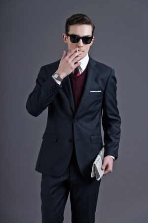 Retro fifties fashion young businessman with black sunglasses wearing dark suit and tie. Smoking a cigarette. Holding a newspaper. Studio shot against grey. photo