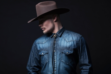 cowboy beard: Modern fashion cowboy. Wearing brown hat and blue jeans shirt. Blonde hair and beard. Studio shot against black. Stock Photo