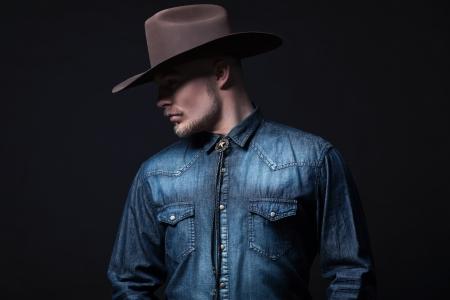 Moderne Mode Cowboy. Braunen Hut und blaue Jeans Shirt. Blonde Haare und Bart. Studio erschossen gegen Schwarz. Standard-Bild - 25226315