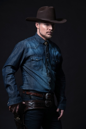 Modern fashion cowboy. Wearing brown hat and blue jeans shirt. Pulling his gun. Blonde hair and beard. Studio shot against black. Stock Photo