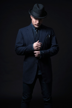 Retro 1900 modern fashion man with blonde hair and beard. Wearing blue striped suit and black hat. Studio shot against black.