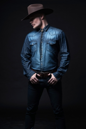 Modern fashion cowboy. Wearing brown hat and blue jeans shirt. Blonde hair and beard. Studio shot against black. Stock Photo