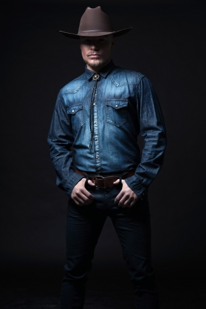 Modern fashion cowboy. Wearing brown hat and blue jeans shirt. Blonde hair and beard. Studio shot against black. Stok Fotoğraf