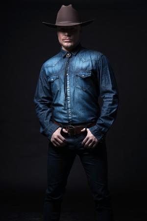 Modern fashion cowboy. Wearing brown hat and blue jeans shirt. Blonde hair and beard. Studio shot against black. Standard-Bild