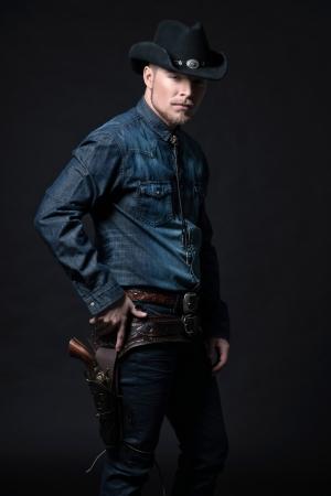 Modern fashion cowboy. Wearing black hat and blue jeans shirt. Pulling his gun. Blonde hair and beard. Studio shot against black.