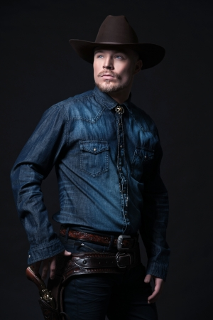 Modern fashion cowboy. Wearing brown hat and blue jeans shirt. Pulling his gun. Blonde hair and beard. Studio shot against black. Stockfoto