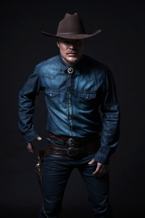 Modern fashion cowboy. Wearing brown hat and blue jeans shirt. Pulling his gun. Blonde hair and beard. Studio shot against black. photo
