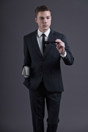 Retro fifties fashion young businessman with newspaper holding black sunglasses wearing dark suit and tie. Studio shot against grey. photo