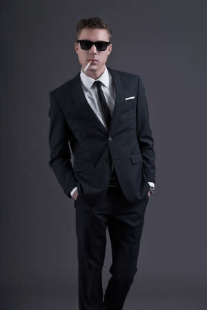 Retro fifties fashion young businessman with black sunglasses wearing dark suit and tie. Smoking a cigarette. Studio shot against grey.