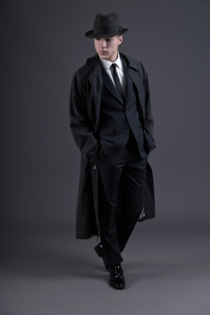 Retro fashion fifties young businessman with hat wearing dark suit and raincoat. Studio shot against grey.