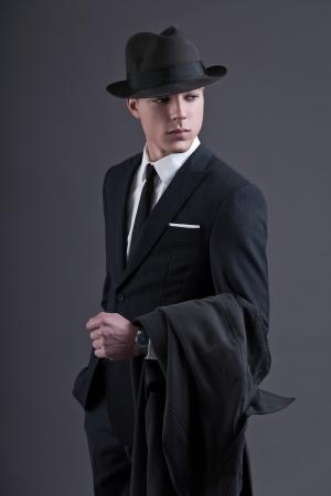 hombre con sombrero: Cincuenta años de la moda retro de empresario joven con el sombrero que llevaban traje oscuro y corbata. La celebración de un impermeable. Foto de estudio sobre gris.