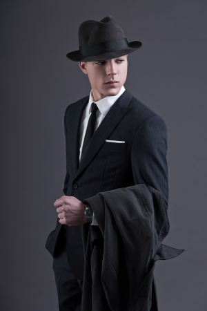 Retro fashion fifties young businessman with hat wearing dark suit and tie. Holding a raincoat. Studio shot against grey.