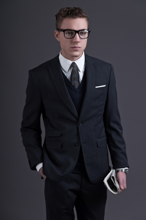 Retro fifties fashion young businessman with black glasses wearing dark suit and tie. Holding a newspaper. Studio shot against grey. photo