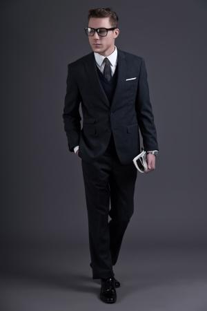 traje: Retro fifties moda joven hombre de negocios con los vidrios negros que llevaban traje oscuro y corbata. La celebraci�n de un peri�dico. Foto de estudio sobre gris.